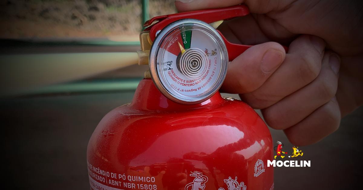 extintor de incêndio residencial - na imagem possui uma mão acionando um extintor de incêndio