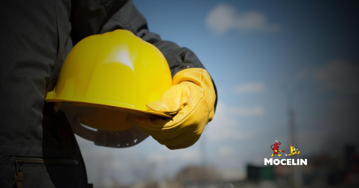 segurança do trabalho na indústria - um homem segurando um capacete amarelo de obra.