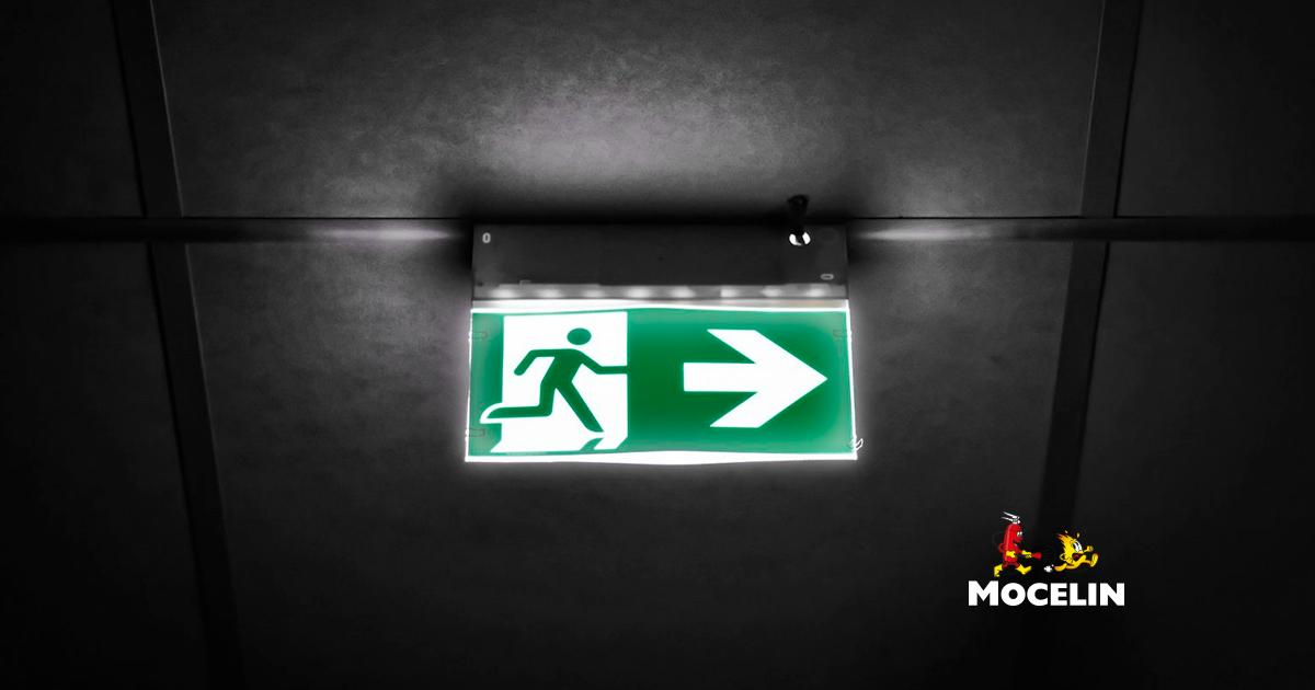 Sinalização de emergência - a imagem mostra uma placa de emergência na cor verde indicando por onde as pessoas devem seguir